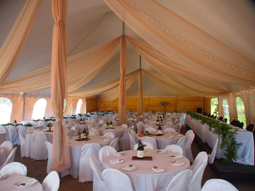 Blush draping and white linens create a elegant dinner atmosphere at The Gardens.