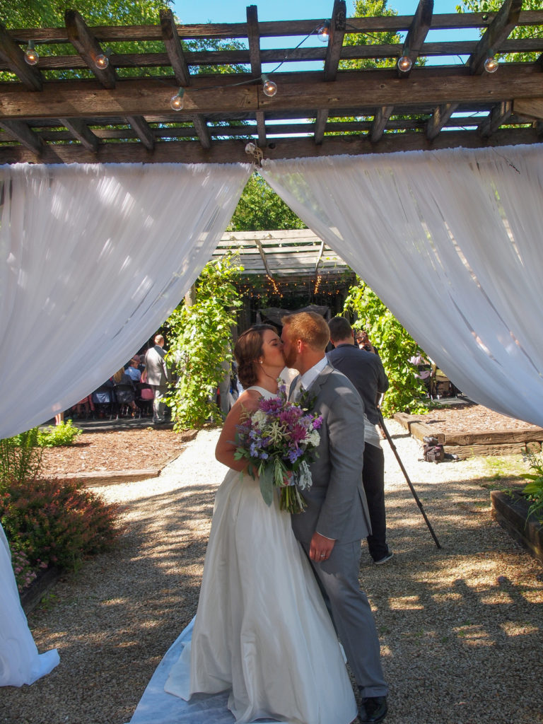 Sealing it with a sweet kiss under the wedding pergola at The Gardens.